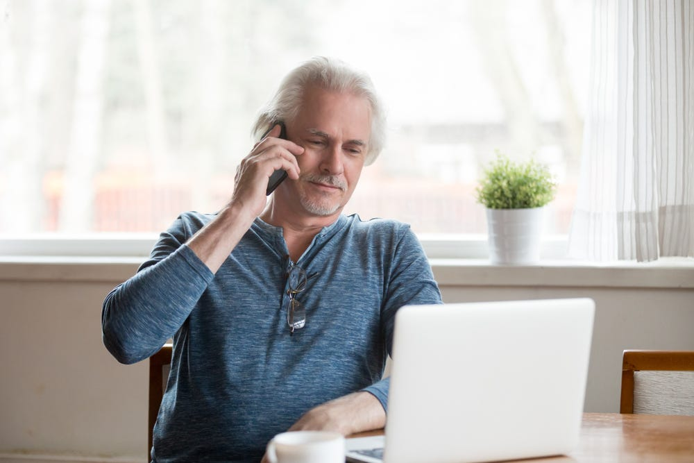 middle-aged man on telephone with laptop open